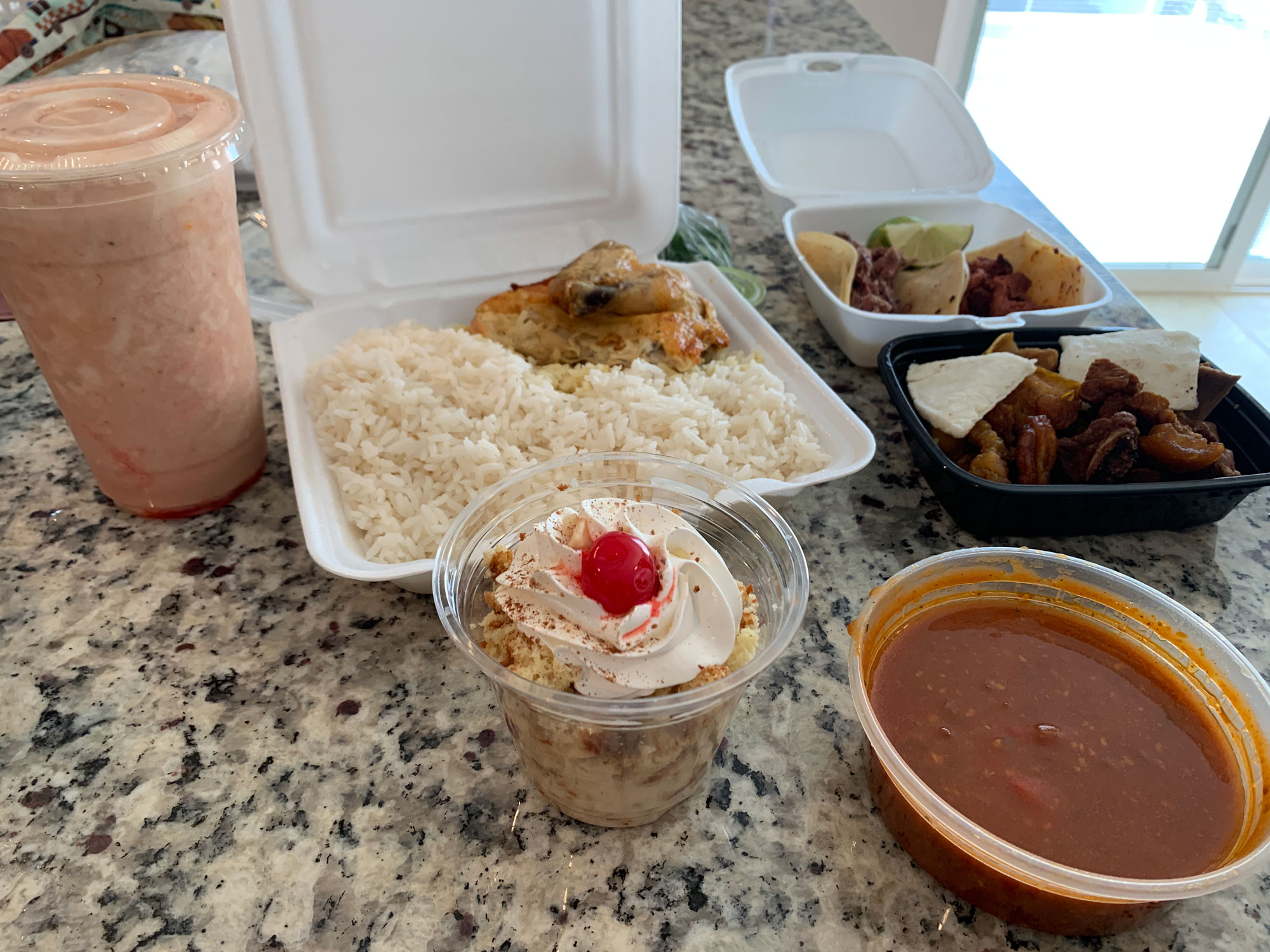 Assorted foods in takeout containers spread on a granite countertop