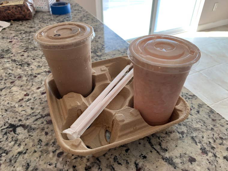 Two chocolate milkshakes in clear plastic cups with still wrapped straws sitting on a countertop