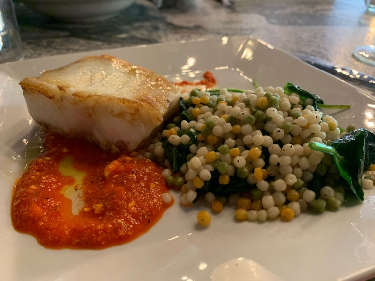 A plate with a cut of fish atop a red pepper sauce with green, white and yellow quinoa on the side