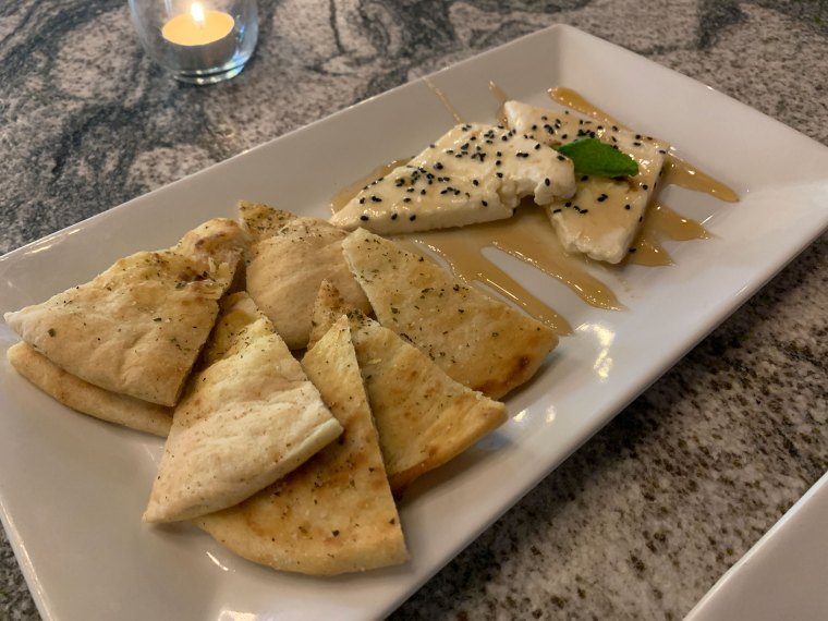 A white rectangular plate, half with pita points the other half with two crescent shaped slices of feta