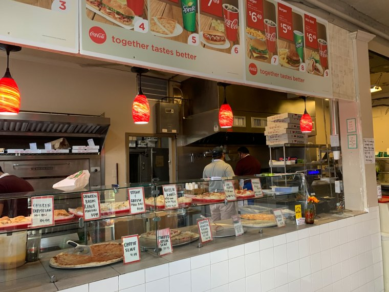 Photo of an order counter in an Italian restaurant. Photos of food are on the wall above the counter while pizza is on display on the counter.