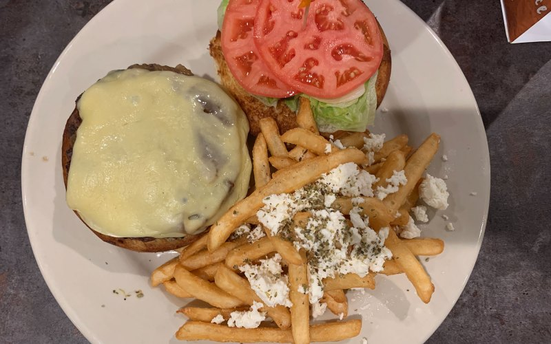 An overhead photo of plate with a burger topped with cheese, the top bun next to it with lettuce and tomato, and a pile of fries.