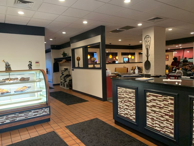 A photo of the entryway of a diner with a hostess stand with painted black wood that matches the trim on the walls.