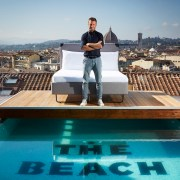 Charlie MacGregor, chief executive officer and founder of The Student Hotel (TSH) at the opening of his first Italian hybrid hotel, TSH Florence Lavagnini. Charlie is pictured standing in front of a bed on a platform above the rooftop pool in front of the Duomo in the Tuscan capital, Florence.