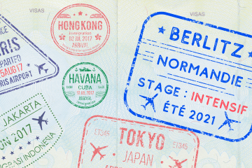 A passport stamped with different entry stamps, including one for Berlitz Normandie.