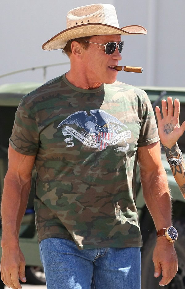 a7685c2398d Arnold Schwarzeneger wore a cowboy hat and a camo shirt that had a bald  eagle and