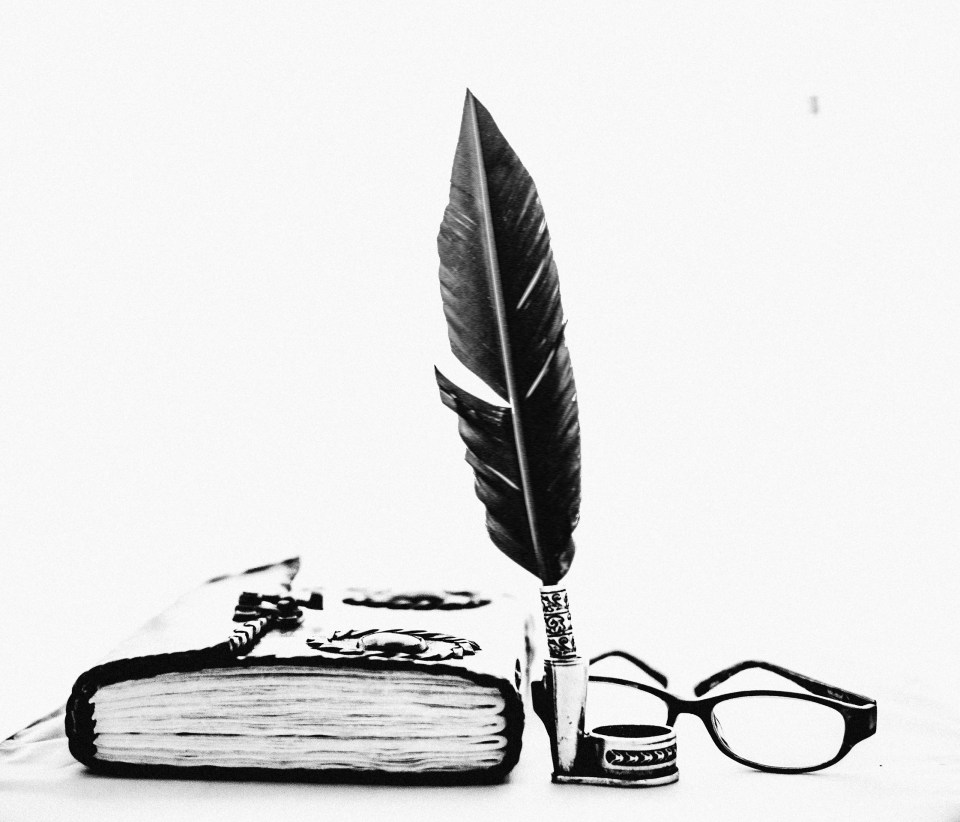 A quill, a book and glasses. Illustrating a post about a creative writing course.