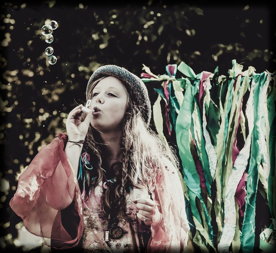 Woman blowing bubbles, fairy ribbons behind her. Turning my memories into poems with her magic.