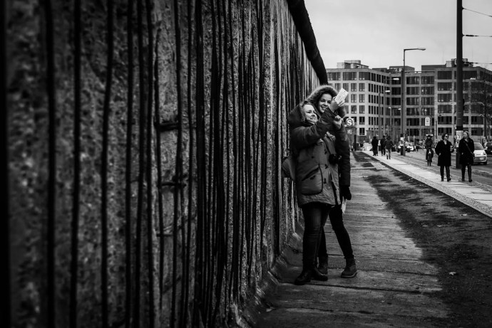 Tourists take a selfie in front of the rests of the Berlin wall
