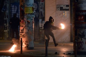 3a69aa6000000578-3937566-a_protester_throws_a_molotov_cocktail_whilst_wearing_a_gas_mask_-a-4_1479247706526