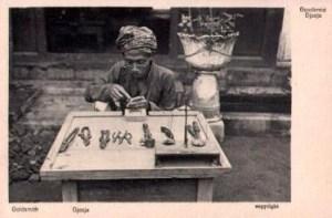 altes sw-Foto: Goldschmied am Tisch sitzend mit Werkzeugen