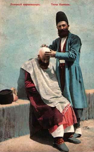 kolorierte Postkarte: Straßenbarbier rasiert Kunden den Schädel