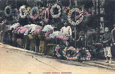 koloriertes Foto: Blumenmarkt mit Kränzen und Sträußen