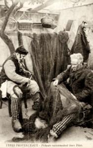 s/w Foto: zwei vor einer Mauer sitzende Fischer bei der Reparatur von Netzen