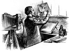 Fotolaborant hält entwickeltes Positiv hoch in die Luft und besieht es sich