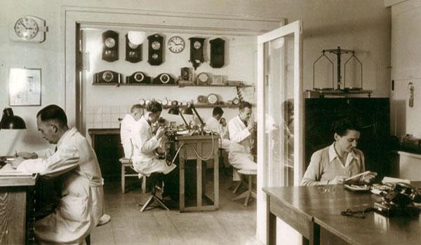sw-Foto: fünf angestellte Uhrmacher und Goldschmiede sowie eine Sekretärin in der Werkstatt bei der Arbeit