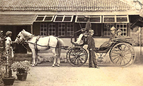 altes Foto: Offizier stehend neben einer offenen Kutsche mit zwei Damen, auf dem Kutschbock ein dunkelhäutiger Kutscher