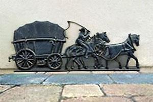 Gußrelief-Bild: Kutsche von drei Pferden gezogen, auf einem davon sitzt die Peitsche schwingend der Kutscher