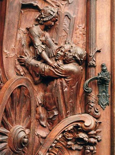 Holztür mit geschnitztem Kutschenmotiv: Zwei Herren helfen einer Dame beim Aussteigen