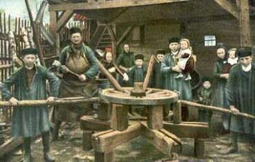 Stellmacher arbeiten am Wagenrad