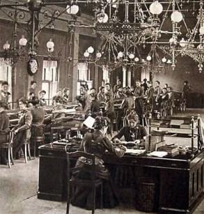 sw Foto: Großraumbüro mit über 30 Telefonistinnen und Telefonisten Tisch an Tisch sitzend bei der Arbeit, vorn rechts an einem Doppelschreibtisch zwei weibliche Aufsichtspersonen, an der Wand eine übergroße Wanduhr im Bahnhofsstil, von der Decke hängens eine opulent gestaltete Gaslichtkonstruktion - 1902