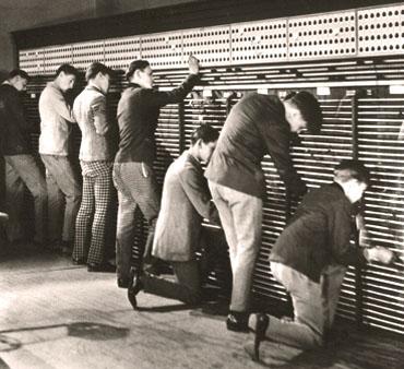 sw Foto: sieben junge Männer arbeiten stehend an Schalttafeln der Telefonvermittlung