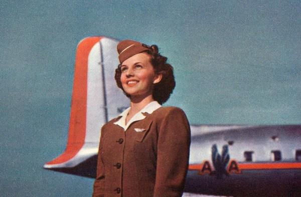 Flugbegleiterin freudig stahlend, jung und schön vor dem Flugzeug stehend