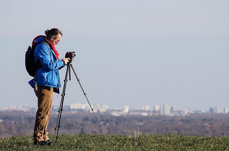 Foto: Fotograf auf einem Hügel mit Kamera auf dem Stativ macht eine Panoramaaufnahme der Stadt