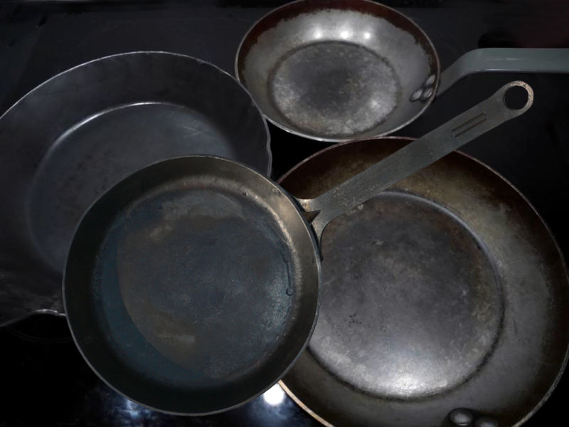 Farbfoto: mehrere Eisenpfannen