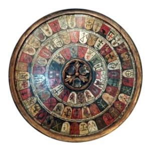 Farbfoto: runde Holztafel in drei runden aufgemalte Wappen zünftiger Schmiede