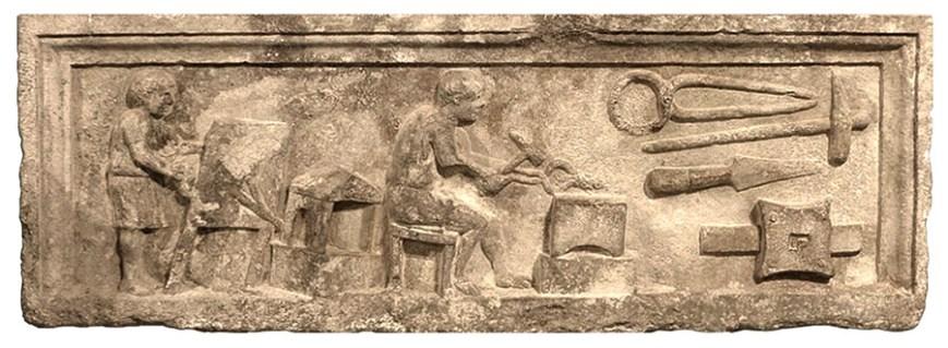Steinrelief: Geselle am Blasebalg vor Feuerstelle, mittig vor Amboss sitzender Schmied ein Hufeisen mit Hammer bearbetend, rechts Werkzeuge
