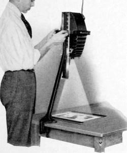 altes sw-Foto: Mann steht am Vergrößerungsgerät