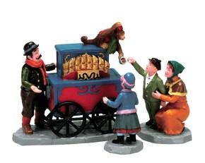 Keramikfiguren: Leierkastenmann mit Affe auf der Drehorgel, der Becher für Münzen herunter hält dazu Mutter mit Junge und Mädchen