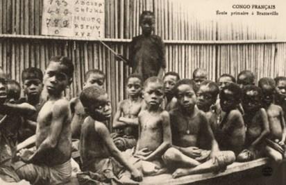 s/w Foto: stehender Junge, der mit Zeigestock auf Pappschild mit Alphabet und Ziffern weist, zwischen mehreren sitzendenSchulanfängern