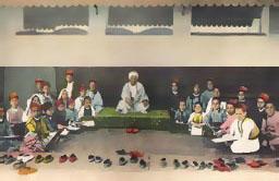 koloriertes Foto: Lehrer mit Turban auf Podest und im Halbkreis darum Schüler am Boden sitzend, im Vordergrund säuberlich aufgereiht die Schuhe aller
