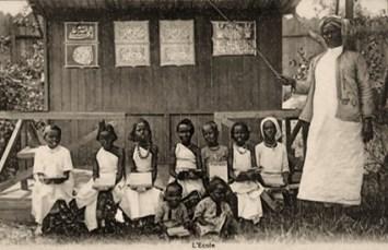s/w Foto: im Freien stehende Lehrerin mit Zeigestock auf als Tafel dienende Bretterwand weisend, davor neun zum Foto aufgereiht sitzende Schülerinnen und Schüler