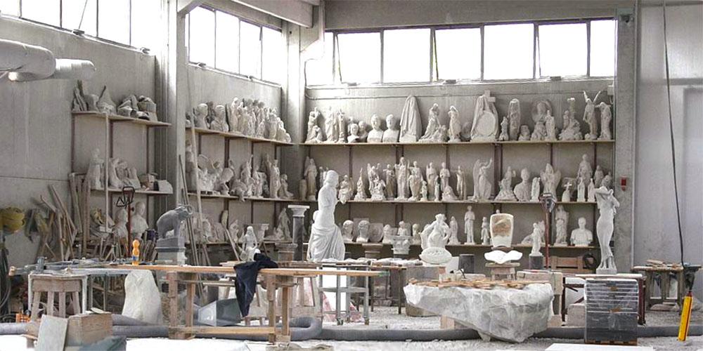 Farbfoto: Blick in eine Bildhauerwerkstatt mit Werkzeugen, Steinblöcken und vielen Skulpturen und Büsten in Regalen an den Wänden