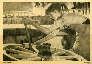 Foto: jugendlicher Handwerker bearbeitet großes Holzrad