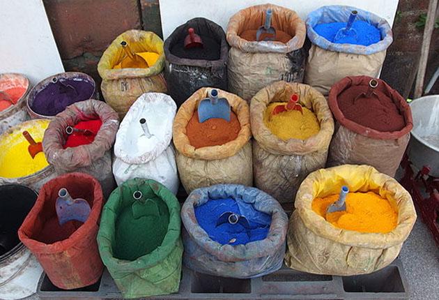 Farbfoto: offene Säcke mit verschiedensten Farbpulvern und Schäufelchen sowie rechts eine Waage
