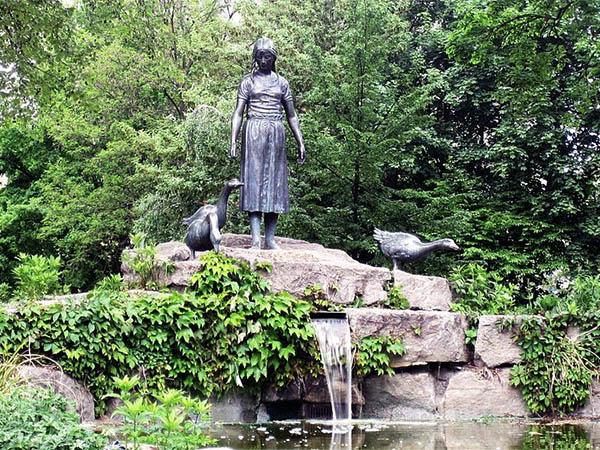 Farbfoto: in Parkanlage auf Felsenplatte stehendes Gänseliesel mit Gänsen, unter der Platte fließt Wasser in einen kleinen Teich