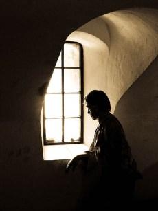 Farbfoto: Gefangener (Puppe) steht am Fenster