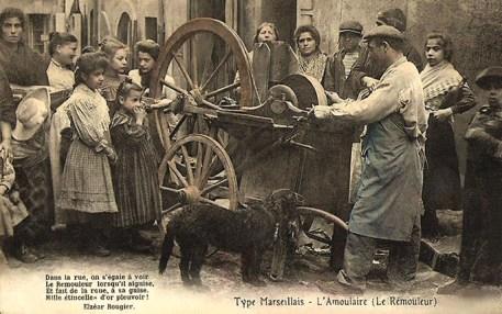 PK: koloriertes Foto: Scherenschleifer arbeitet auf der Straße umringt von vielen Leuten