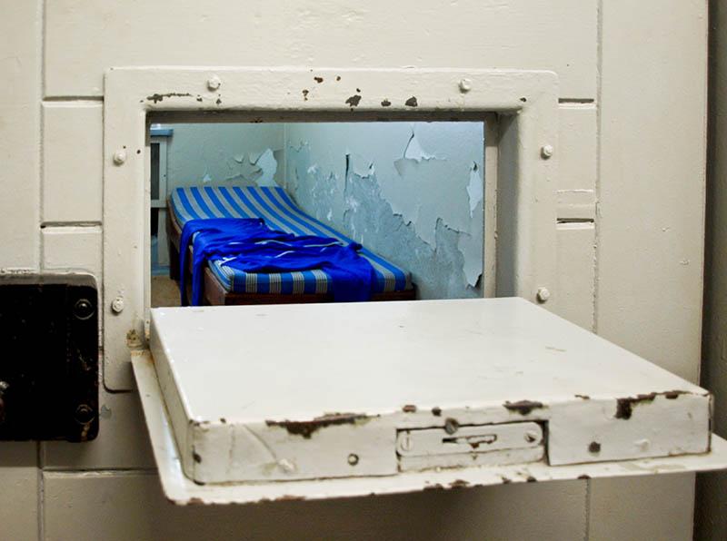 Farbfoto: Einblick durch geöffnete Gefängnistürklappe in die Zelle. Dort steht ein einfaches Bett mit Matratze.