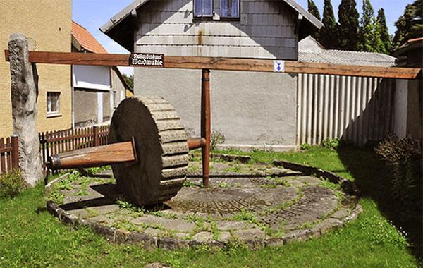 Farbfoto: runder Waidmühlplatz mit Mahlvorrichtung nebst großem runden Mühlstein, der aufrecht benutzt wurde