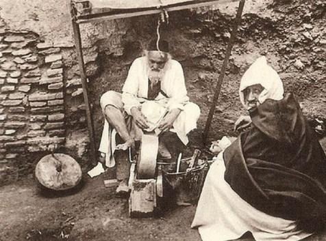 altes s/w-Foto: jenischer Messerschleifer sitzt am Schleifstein am Boden, davor sitzt wohl ein Kunde