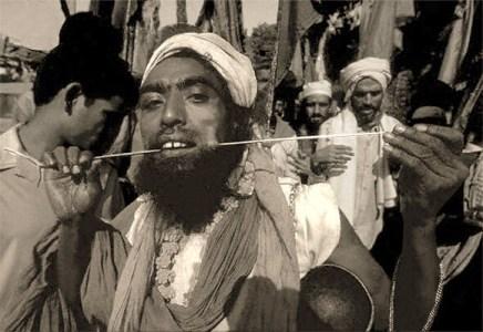 sw Foto: Mann durchsticht seine Wange mit langem Spieß