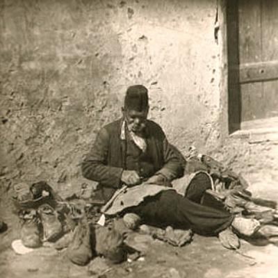 sw Foto: alter Schuster sitzt arbeitend am Boden vorm Haus - Türkei, 1930