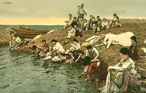 koloriertes Foto: Waschfrauen am Strand und viele Kinder