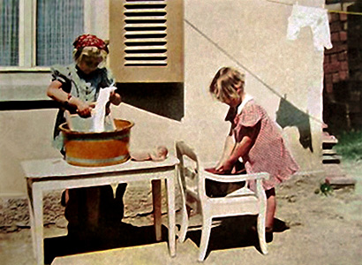Farbfoto: zwei Mädchen waschen Puppenwäsche