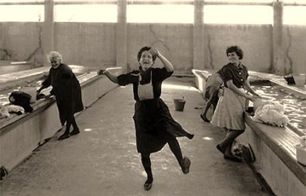 sw Foto: zwischen Wäscherinnen an Steinwaschbecken mit Rubbelschrägen tanzt eine von ihnen